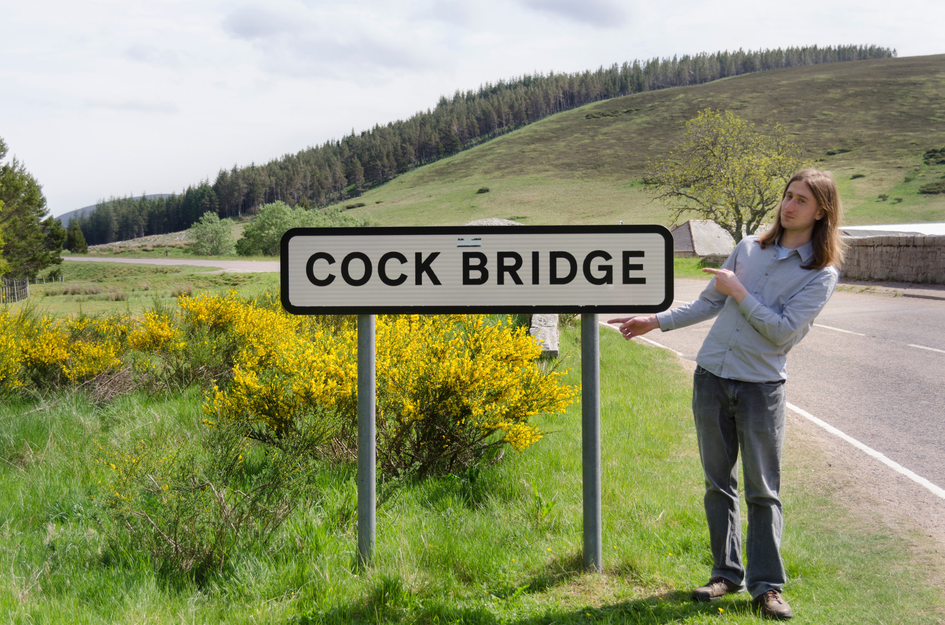 Photo of Cock Bridge with me pointing to the sign